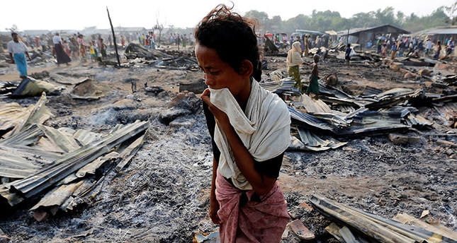 A woman walks among debris after fire destroyed shelters at a camp for internally displaced Rohingya Muslims in the western Rakhine State near Sittwe